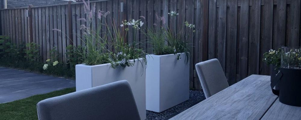 Hoge witte plantenbakken - eenvoudig je eethoek in de tuin afscheiden van het zitgedeelte