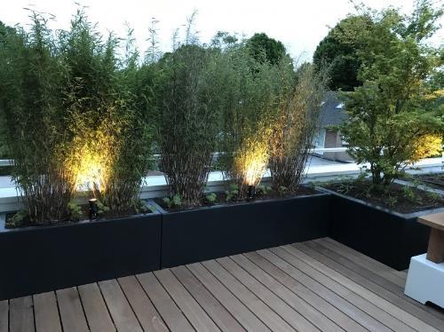 Antraciet-zwarte plantenbakken verwerkt op een dakterras.